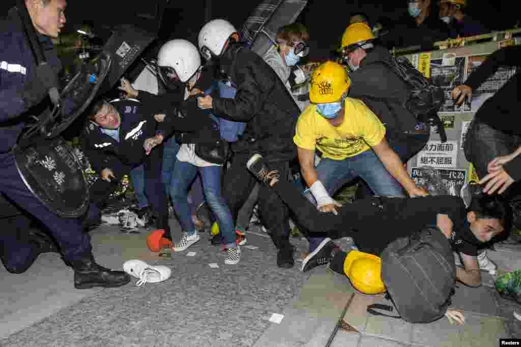 Seorang demonstran jatuh ketika dikejar oleh polisi anti huru-hara di Badan Legislatif di Hong Kong, pagi hari Rabu, 19 November 2014.