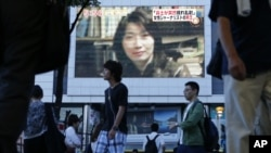 An image of Japanese journalist Mika Yamamoto is shown on a large monitor screen in Tokyo during a TV news broadcast reporting her death in Syria, August 21, 2012.