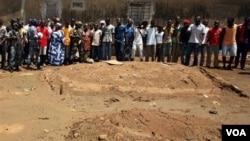 Warga setempat ikut menyaksikan penggalian lokasi yang dijadikan kuburan massal korban kekerasan di ibukota Abidjan (5/5).