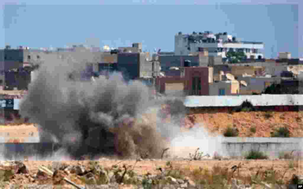 An explosion is seen near Muammar Gadhafi's main compound in the Bab al-Aziziya district in Tripoli, Libya, Tuesday, Aug. 23, 2011. Fresh fighting erupted in Tripoli on Tuesday hours after Moammar Gadhafi's son turned up free to thwart Libyan rebel claims