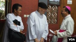 Uskup Agung Semarang Mgr. Robertus Rubiyatmoko menyapa Romo Karl Edmund Prier (tengah) korban luka di kepala akibat penyerangan gereja St.Lidwina, Minggu 11/2 lalu. (Foto: VOA/Munarsih)