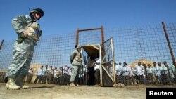 Binh sĩ Mỹ đứng gác trong khi tù nhân Iraq chờ được phóng thích tại nhà tù Abu Ghraib, phía tây Baghdad, 23/6/2006.