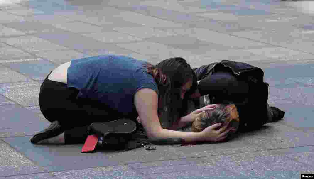A woman attends to an injured man on the sidewalk in Times Square after a speeding vehicle struck pedestrians on the sidewalk in New York City.