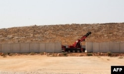 A picture taken in the Syrian village of Kafr Lusein, north of the Bab al-Hawa border crossing, Oct. 7, 2017, shows a crane parked next to a 3-meter-high fortification, built by the Turkish government along its border with Syria. The Britain-based Syrian Observatory for Human Rights monitor said Turkish army cranes had begun removing sections of the security wall Turkey has built on the border in preparation for an incursion.