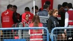 Migrants et policiers à quai dans le port Dikili, sur l'île grecque de Chios en Turquie, le 4 avril 2016. (AP Photo/Emre Tazegul)