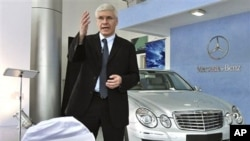 DaimlerChrysler India Managing Director and Chief Executive Officer Wilfried Aulbur stands next to a Mercedes E-280 as he speaks during an event
