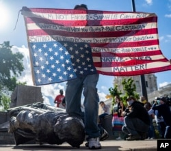 Gabriel Black Elk, who is Lakota, kneels on the neck of a fallen statue of Christopher Columbus and holds an American flag with the names of Native Americans killed by police, at the Minnesota state Capitol in St. Paul, Minn., June 10, 2020. (Evan Frost)