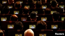 People watch South Korean President Park Geun-hye's speech on small screens fitted in their seats during a ceremony celebrating the 96th anniversary of the Independence Movement Day in Seoul, March 1, 2015.