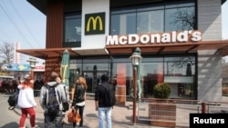 Warga berkumpul di luar salah satu restoran McDonald's di Simferopol, Krimea (4/4). Restoran cepat saji ini menutup operasi tiga gerainya di wilayah Krimea.