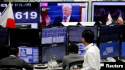 Employees of a foreign exchange trading company work near monitors showing President Donald Trump and the Japanese yen's exchange rate in Tokyo, January 23, 2017.