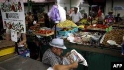 Prodavac na pijaci čita novine dok čeka kupca. Za nekoliko dana počinju razgovori srpske vlade i predstavnika MMF-a o eventualnoj obnovi sedmog, poslednjeg kreditnog stend baj aranžmana