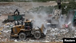 A truck unloads garbage at a landfill at Tseung Kwan O district in Hong Kong, China, June 9, 2017.