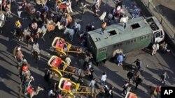 开罗解放广场上支持穆巴拉克者骑马骑骆驼坐马车,旁为冲突中被烧的警车