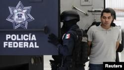 La policía federal mexicana escolta a Bogard Lugo (derecha), acusado de ser uno de los causantes de la balacera en el aeropuerto de la Ciudad de México.