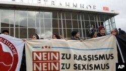 """Quelques personnes manifestent en face de la gare centrale de Cologne, en Allemagne, le mercredi 6 janvier 2016, avec une affiche mentionnant : """"Non au racisme, Non au sexisme""""."""