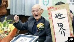 Chitetsu Watanabe (112), berpose di sebelah kaligrafi yang ia tulis setelah dianugerahi sebagai lelaki tertua di dunia oleh Guinness World Records, di Joetsu, prefektur Niigata, Jepang utara Rabu, 12 Februari 2020. (Kyodo News via AP)