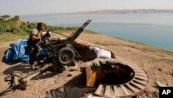 Un combatiente peshmerga kurdo prepara un cañón en una trinchera cerca de la presa de Mosul, retomada por los kurdos.
