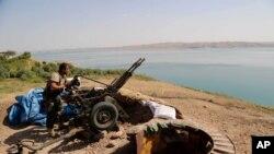 Một chiến binh người Kurd chuẩn bị võ khí tại một địa điểm tác chiến gần Đập Mosul