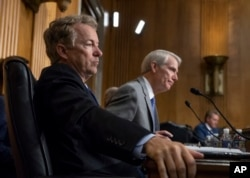 Sen. Rand Paul, R-Ky., left, and Sen. Rob Portman, R-Ohio, pose questions to witnesses as the Senate Committee on Foreign Relations holds a hearing on relations between the U.S. and Russia, in Washington, Aug. 21, 2018.