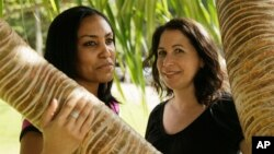 FILE - Taeko Bufford, left, and Diane Cervelli are pictured near Waikiki Beach in Honolulu, Dec. 19, 2011. A Hawaii court ruling that a bed and breakfast discriminated against the couple brcause they're gay will stand; the state and U.S. high courts both declined to hear appeals.
