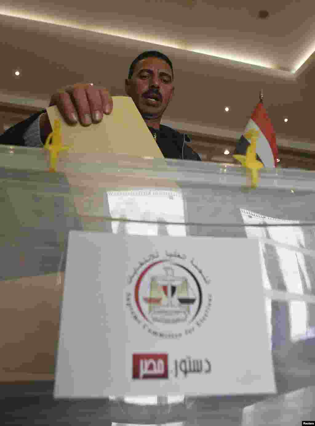 An Egyptian votes on the new Egyptian constitution at the Egyptian embassy in Amman December 12.