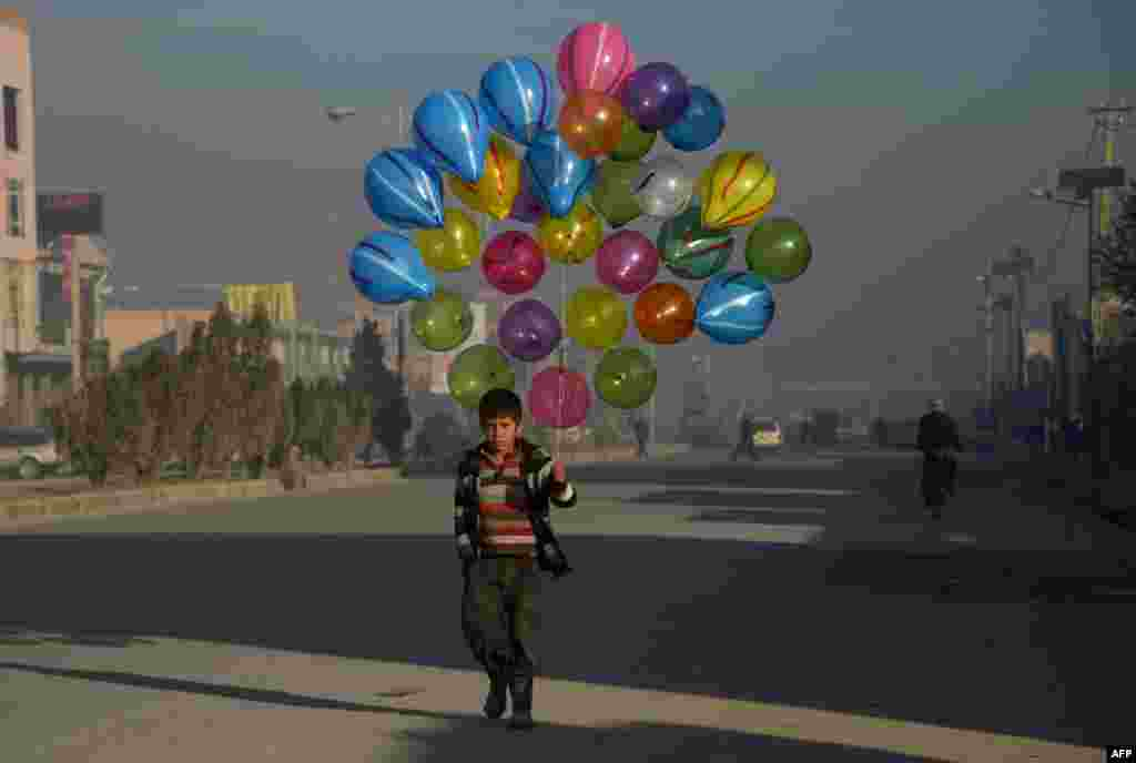 Afghan boy Hizbullah, 10, walks as he looks for customers to buy his balloons on the streets of Mazar-i-Sharif.