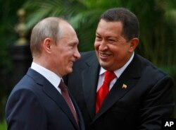 FILE - Venezuela's President Hugo Chavez, right, and Russia's Prime Minister Vladimir Putin speak during a welcoming ceremony at Miraflores Presidential Palace in Caracas, April 2, 2010