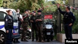 Police and soldiers secure the scene where French soliders were hit and injured by a vehicle in the western Paris suburb of Levallois-Perret, France, Aug. 9, 2017.
