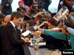 "Actor Eddie Redmayne signs autographs during the red carpet event for the movie ""The Danish Girl"" at the 72nd Venice Film Festival, northern Italy, Sept. 5, 2015."