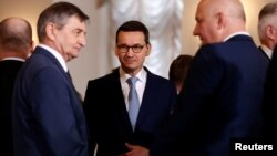 Poland's Prime Minister Mateusz Morawiecki speaks with Marek Kuchcinski (L), speaker of parliament and Joachim Brudzinski, newly sworn-in Interior Minister after a ceremony at Presidential Palace in Warsaw, Jan. 9, 2018.