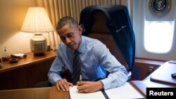 Tổng thống Barack Obama ký hai văn bản tổng thống liên quan đến sắc lệnh hành pháp về di trú trong khi di chuyển đến Las Vegas, Nevada, trong chiếc chuyên cơ Air Force One, 21/11/2014.