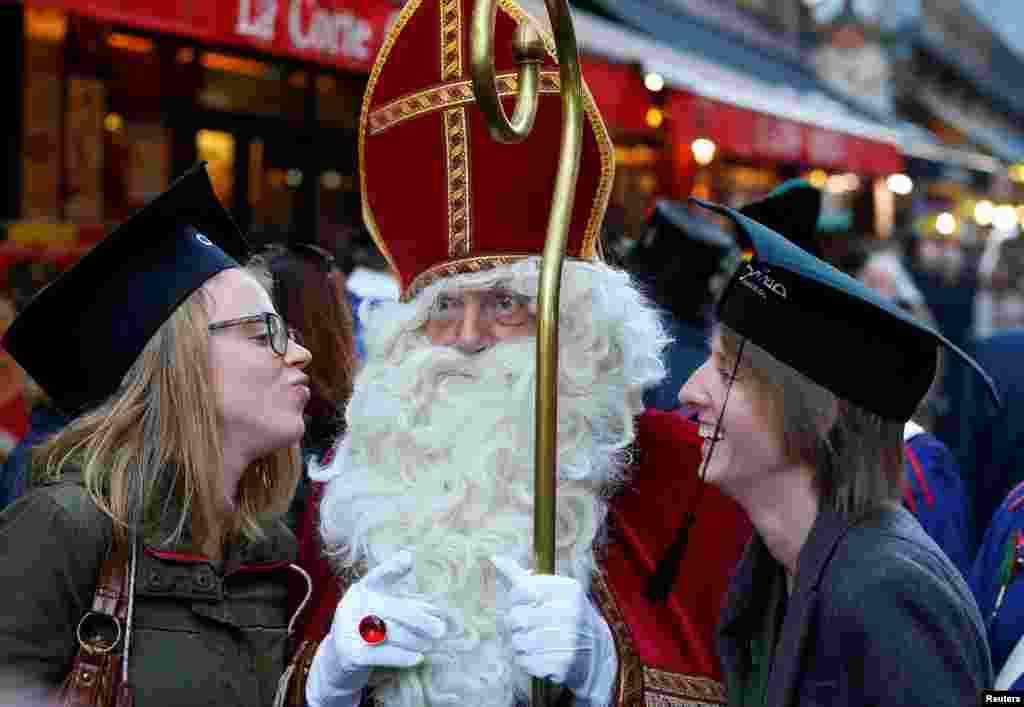 Saint Nicholas poses with students during a traditional parade in central Brussels, Belgium, Dec. 3, 2016.