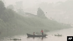 FILE - A man rows a boat on Siak River as thick haze from wildfires blanket the city in Pekanbaru, Riau province, Indonesia, Oct. 5, 2015.
