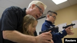 Thầy giáo Jerry Kau hướng dẫn cô bé Joanna Zuber sử dụng súng tại lớp học Sử dụng súng an toàn dành cho thiếu niên ở tiểu bang Illinois, ngày 21/4/2015.