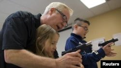 FILE - Instructor Jerry Kau shows student Joanna Zuber how to load a magazine into a handgun alongside Sam Minnifield during a Youth Handgun Safety Class at GAT Guns in East Dundee, Illinois, April 21, 2015.