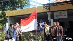 Koalisi Masyarakat Sipil Peduli Kedaulatan Rakyat Jawa Timur kibarkan bendera Merah Putih setengah tiang atas pengesahan UU Pilkada oleh DPR yang mengembalikan pemilihan langsung oleh rakyak kepada DPRD (Foto: VOA/Petrus)