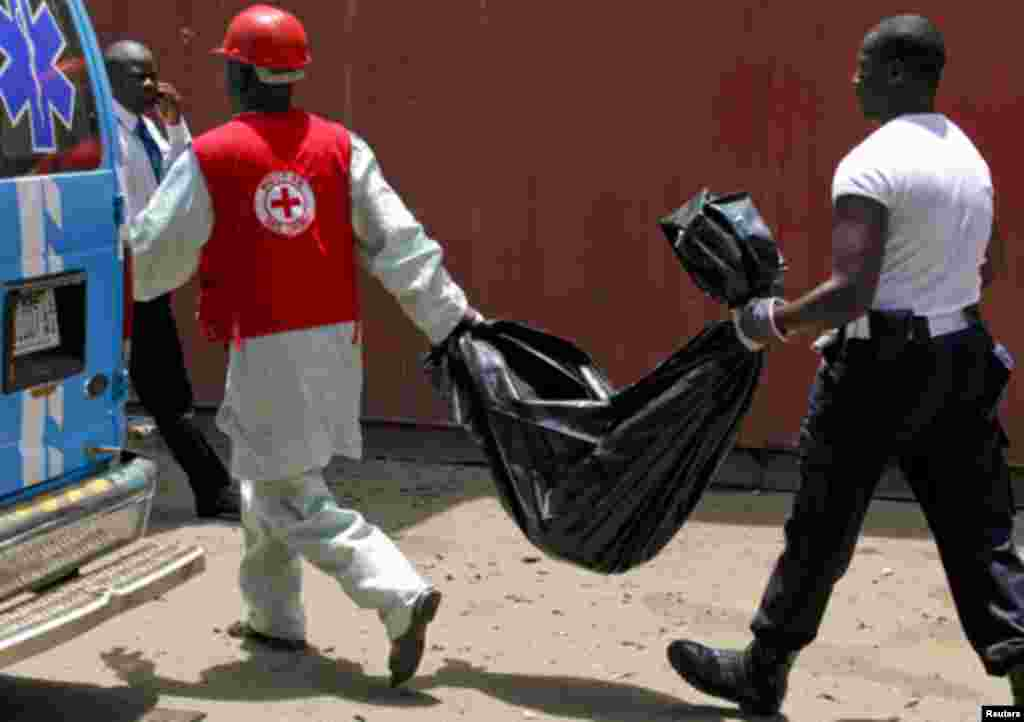 Rescue officials recover mangled bodies, wrapped in black polythene, at the site of a bomb blast at the premises of Nigerian newspaper This Day in Abuja April 26, 2012