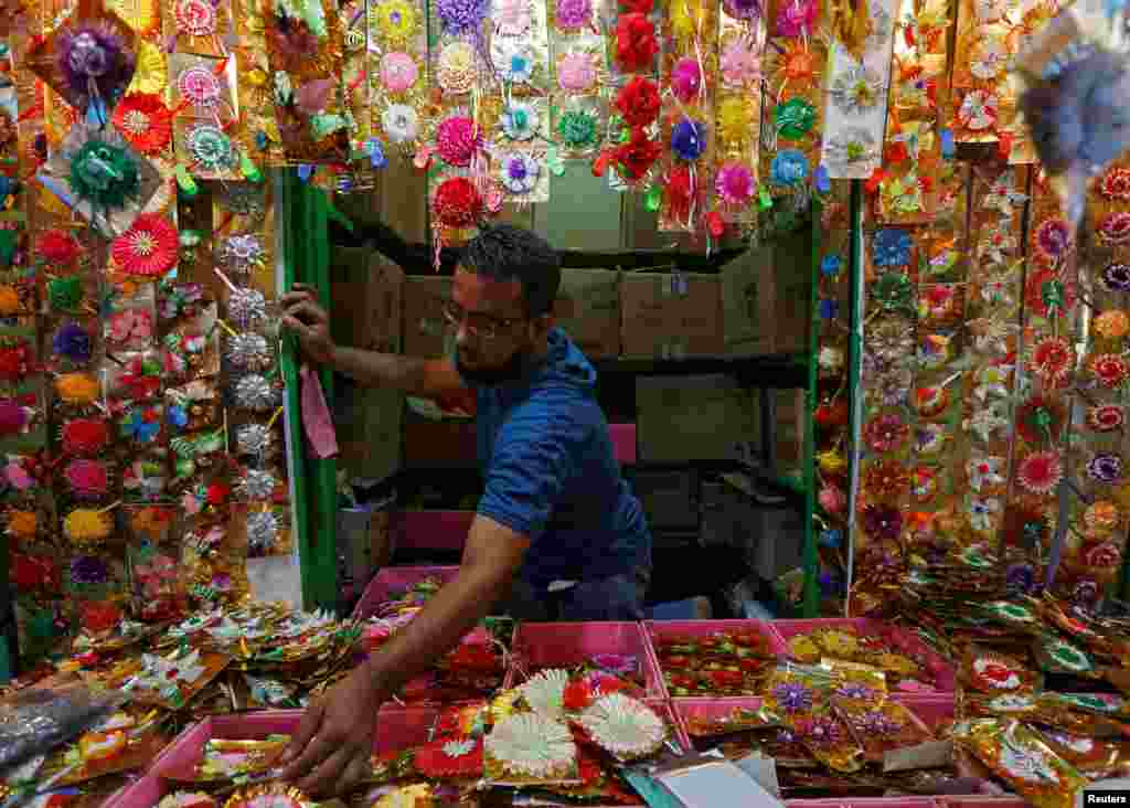 "A man arranges ""Rakhis"" or sacred threads as he waits for customers at his roadside stall ahead of the Hindu festival Raksha Bandhan celebrations, in Kolkata, India."