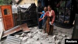 Warga meninggalkan rumahnya yang rusak karena gempa di kabupaten Bener Meriah (2/7). (Foto: Reuters)