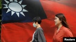 人们从台北街头的台湾旗帜旁走过。(2020年8月10日)