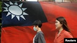 人們從台北街頭的台灣旗幟旁走過。(2020年8月10日)