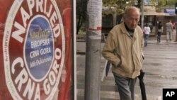 """Seorang pria melewati poster bertuliskan """"Maju Terus, Montenegro"""" di pusat kota Podgorica, Montenegro, (Foto: dok). Montenegro menggelar pemilu hari ini, Minggu (14/10)."""