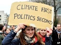"""Una manifestante sostiene un cartel que dice """"El clima primero, luego la política"""", durante una marcha en Bruselas el domingo 2 de diciembre de 2018."""