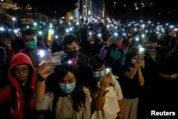 Protesters raise their mobile phones with lights on as they gather to show their support for protersters who are still inside the campus of the Hong Kong Polytechnic University (PolyU) in Hong Kong, China, November 19, 2019.