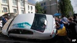 수송기 격추 사건으로 분노한 우크라이나인들이 러시아 대사관 인근에 주차된 승용차를 넘어뜨리며 시위를 벌이는 모습.