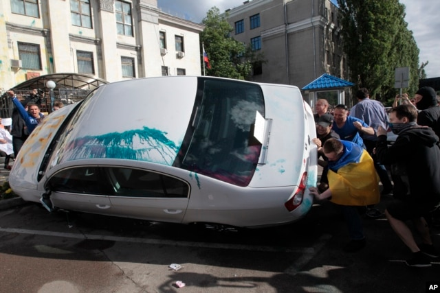 Ukrainian protesters turn over cars near the Russian Embassy during a rally in Kyiv, Ukraine, June 14, 2014.