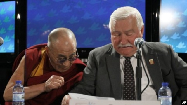 The Dalai Lama, right, looks at the remarks of Lech Walesa, former president of the Republic of Poland, during a news conference after the final session of the World Summit of Nobel Peace Laureates, Chicago, April 25, 2012.