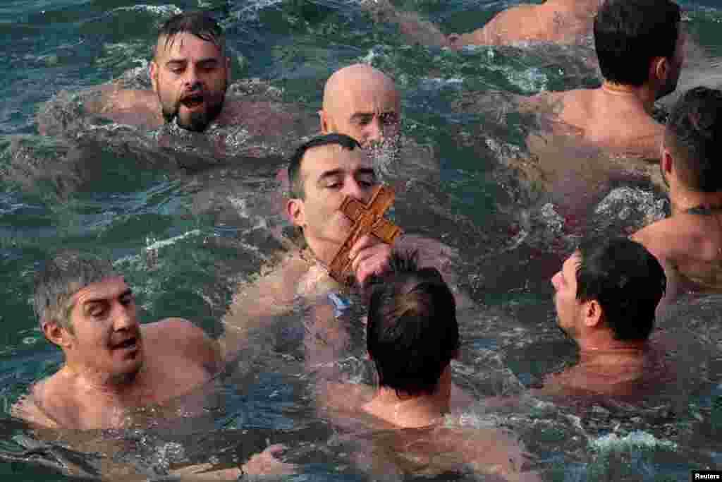Seorang pria Ortodoks yang setia mencium kayu salib saat berlangsungya perayaan Epiphany di Thessaloniki, Yunani.