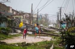 Ljudi hodaju duž oborene električne instalacije koju je uništio uragan Irma, na Karibima, Kuba, 9. septembra 2017. Nema izveštaja o smrtnim slučajevima i povređenima.