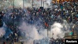 Para penggemar tim Argentina lari dari semprotan gas air mata dalam bentrokan dengan polisi di Buenos Aires, menyusul kekalahan tim itu dari Jerman di Brazil (13/7). (Reuters/Ivan Alvarado)